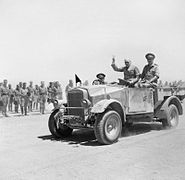 Winston Churchill giving his famous V-for-Victory sign while being driven past a line of troops in Tel-el-Kebir, 9 August 1942. E15387.jpg