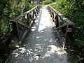 Wooden footbridge over Füzes Stream at Patak Street, Torbágy, Hungary.jpg