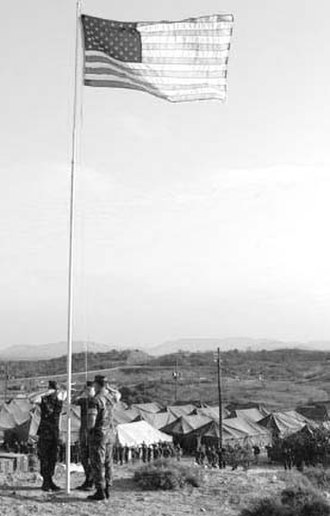 "1st Battalion, 2nd Marines - Marine CPL's David J. Docimo, Austin Quehl and Dustin Bray with Bravo Company 1/2, raise the US Flag for the 1st time over ""Freedom Heights"" Camp X-Ray Cuba 2002"