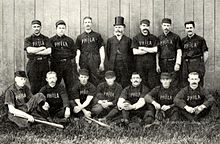 "Two rows of men wearing old-style dark-colored baseball uniforms with ""PHILA"" on the chest; in the rear center stands a bearded man with a high dark top hat and a Victorian-era suit"