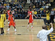 a man in a white shirt makes a signal to basketball players on the court with his fist in the air from the sidelines. He is viewed from behind.