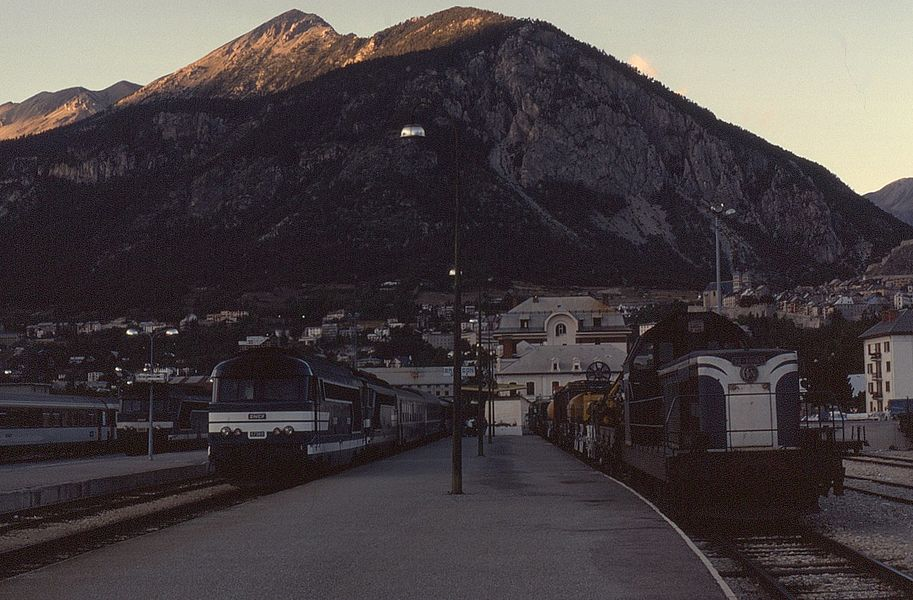 Evening sunset at the Alpine branch terminus station of Briançon which has seen a variety  loco hauled trains over the years. These include overnight trains to Paris as well as many additional ones during the winter sports season. On 28 August 1989, double headed BB67560 (nearest the camera) and BB67309 are the power for the 19:55 to Paris Gare de Lyon which they will work as far as Valence. To the right is BB66127 on an engineers train.