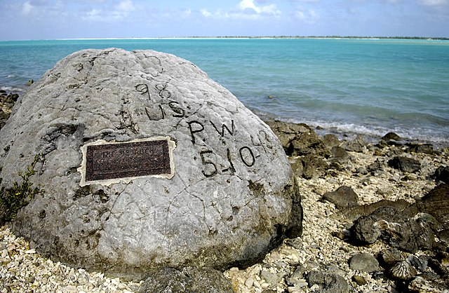 "The ""98 Rock"" is a memorial for the 98 U.S. civilian contract POWs who were forced by their Japanese captors to rebuild the airstrip as slave labor, then were blind-folded and killed by machine gun Oct. 5, 1943. An unidentified prisoner escaped, and chiseled ""98 US PW 5-10-43"" on a large coral rock near their mass grave, on Wilkes Island at the edge of the lagoon. The prisoner was recaptured and beheaded by the Japanese admiral, who was later convicted and executed for war crimes. (U.S. Air Force photo/Tech. Sgt. Shane A. Cuomo)"