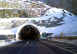 Tunnel portal in a snow covered slope, traffic sign indicating name of the tunnel is visible to the right of the entrance to the tunnel