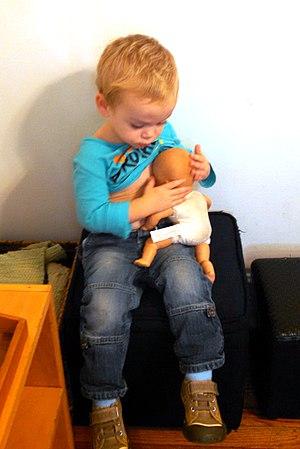 Make believe - A boy pretending to nurse his doll.