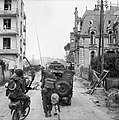 A jeep and other vehicles and troops passing through La Breche as they move inland from Sword Beach, Normandy, 6 June 1944. B5036.jpg