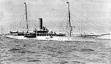 A black and white image of a twin-masted motor yacht with a funnel afloat with no sails set.
