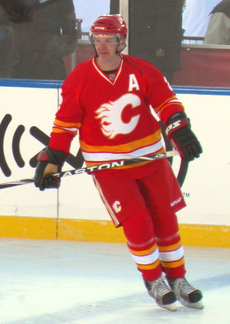 "An ice hockey player looks to his right as he glides across the ice.  He is in a red uniform with white and yellow trim, with a stylized ""C"" logo on his chest."