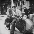American officer and French partisan crouch behind an auto during a street fight in a French city. - NARA - 531322.tif