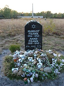 Sebuah Monumen untuk Margot dan Anne Frank yang menampilkan Bintang Daud dan nama lengkap, tanggal kelahiran, dan tanggal kematian masing-masing dari bersaudari tersebut, in white lettering on a large black stone. The stone sits alone in a grassy field, and the ground beneath the stone is covered with floral tributes and photographs of Anne Frank