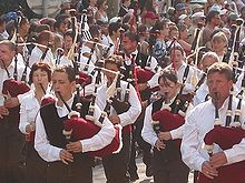 Group of young men and women, wearing white shirts (some with black waistcoats) and black trousers, marching in a parade, in the sunshine. Each is playing a set of bagpipes. The bags are claret in color. The entire picture is full of people. Those not taking part in the parade are watching the procession.