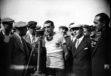 Photographie en noir et blanc montrant un cycliste parlant dans un micro, entouré par plusieurs personnes.