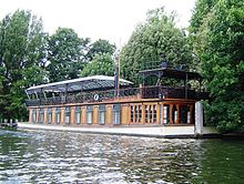 A large, low-slung boat lies moored on the bank of a body of water.  The lower deck is made from wood, interrupted by several large windows.  The upper deck is made from decorative metal, and covered with a large glass awning.