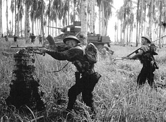 Marching fire - Australian troops advance against a Japanese pillbox in 1943, supported by an M3 Stuart tank