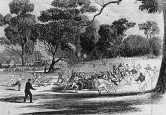Australian rules football in Victoria - A game at the Richmond Paddock in the 1860s. A pavilion at the MCG is on the left in the background. (A wood engraving made by Robert Bruce on 27 July 1866.)