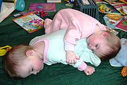 Eight month old fraternal twin girls napping.