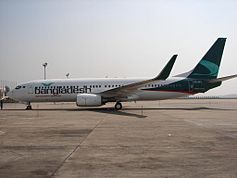 A white aircraft with Bangladesh written in green on the front half below the windows with a dark green colour on the tail facing left