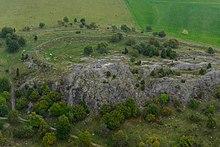 Photo d'un terrain comprenant un rempart bas et l'affleurement d'un rocher.