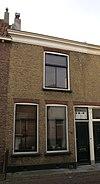 foto van Woonhuis van parterre en verdieping onder een dak met het nr. 5. Blauwe stoep. Achtergevel belangrijk voor situatie van de kerk