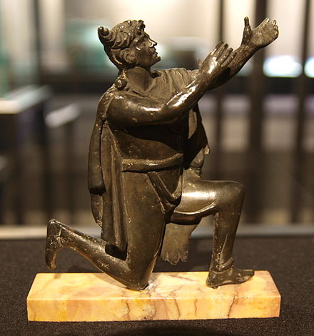 Roman bronze figurine, which depicts a praying Germanic man with a characteristic Suebian knot. Bronze figure of a German Bibliotheque Nationale.jpg