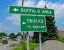 "Two green signs on metal poles with white lettering and arrows pointing to the left. The larger one says ""Buffalo area"" and the smaller says ""Trucks to Warsaw"". There is a road behind it to the left leading to an intersection at the rear."