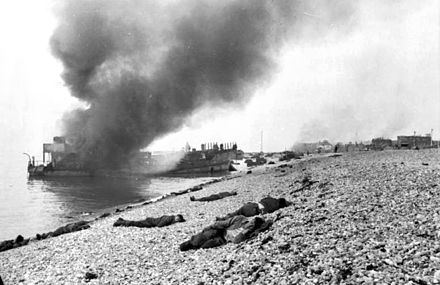 Landing craft on fire, Canadian dead in the foreground. A concrete gun emplacement on the right covers the beach; the steep gradient can clearly be seen. Bundesarchiv Bild 101I-291-1229-12, Dieppe, Landungsversuch, tote alliierte Soldaten.jpg