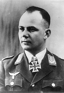 A man wearing a military uniform with an Iron Cross displayed at his neck.