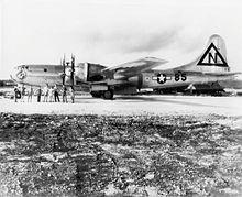 Et skinnende metalmotor med fire motorer står på en landingsbane.  Besætningen stiller sig foran den.