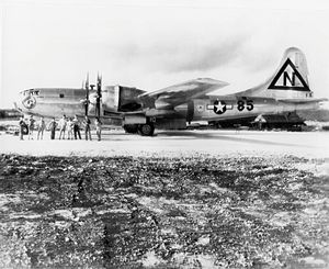 A shiny metal four-engined aircraft stands on a runway. The crew pose in front of it.