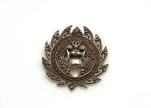 Bhoma - The bhoma in a silver brooch.