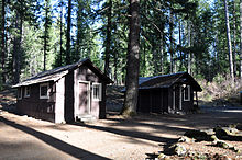 Two small cabins in the woods face a dirt road.