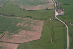 Aerial photograph of fields, with a less-than-straight country lane passing up close to the right hand side. In the top of the frame a modern farmhouse and buildings stand on right of the road. Most of the land is pasture, with two arable fields visible. The crop there is sparse, with large bare patches. The brook wiggles across the upper half of the picture, serpentine in a landscape of straight boundaries. It is narrow and from this height and angle the water surface cannot be discerned. The spring is centre right, its own water course straight and running upwards,toward the brook. The spring is in the greenest of the meadows, with the low humps and bumps of the lost village around.