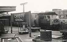 "A black-and-white photograph of a railway platform. Two trains stand side-by-side on the image's right while a sign on the platform reads ""Cardiff (General)"". A formally dressed gentleman stands on the platform, looking away from the viewer. A briefcase, presumably his, rests on a small trolley beside him"