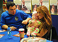 Carlos Mencia and Jessie James take time from signing autographs to hold Carys Wigginton, 5 months, at the RAF Lakenheath Base Exchange.jpg