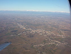 A plane view of Cervignano and Terzo di Aquileia; the Alps in the background.