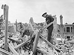 Civil Defence wardens and a member of the American Ambulance Great Britain search amongst rubble for salvageable items following a V1 Flying Bomb strike in Upper Norwood, south London during 1944. D21232.jpg