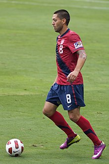 A man wearing a red shirt and blue short pants readies to kick a soccer ball