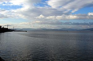 The River Clyde opening out at Newark Castle, Port Glasgow past Clydeport Ocean Terminal, Greenock, to the Firth of Clyde on the left, and to the right past Ardmore Point to the Gare Loch.