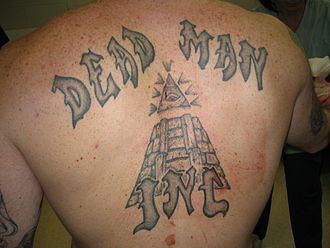 Dead Man Incorporated - Gang's name tattooed on a member's back.