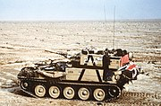 small armoured vehicle alone in the desert. The flag of the United Kingdom can just be seen on the rear