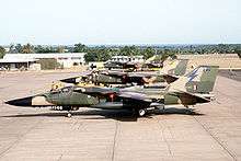 Side view of jets in two-tone green camouflage livery parked side-by-side on ramp.