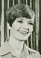 A woman in her thirties with short, parted hair in a black-and-white portrait shot.  She wears a khaki shirt.