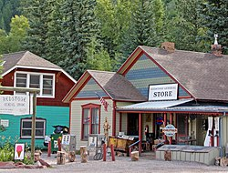 "A colorful one-and-a-half-story wooden building with a pointed wooden shingled roof and large signs on the front and in front reading ""Redstone General Store"". There are some old gas pumps out front. To the left is another house in a mixture of colors."