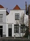 foto van Sint Christoffel. Huis met gepleisterde ingezwenkte gevel, lijst met klosjes. Staafankers. Voordeuromlijsting