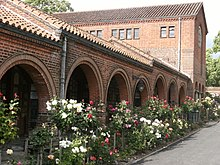 A brick cloister, built in a modified Lombard-Romanesque style