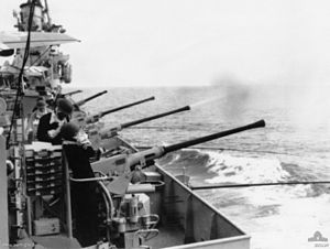 The flank of a ship. Several long-barrelled guns are aimed over the side, and are being operated by sailors. One of the guns has just fired, with a cloud of smoke issuing from the barrel.