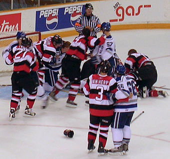 Altercations often occur near the goal after a stoppage of play, since defensive players are highly concerned with protecting their goaltender, seen here in a match between Ottawa and Sudbury of the Ontario Hockey League. Hockeyfight.JPG