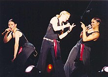 Picture of three woman. The one in the middle has her blonde hair tied in a ponytail. She holds a microphone on her left arm and is leaning towards her right and pointing towards an African American female who's pointing back at her. On the left there's a caucasian female holding a microphone with her left hand.