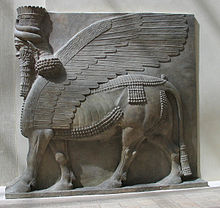 Assyrian relief sculpture of a Lamassu - a winged bull with a bearded human head