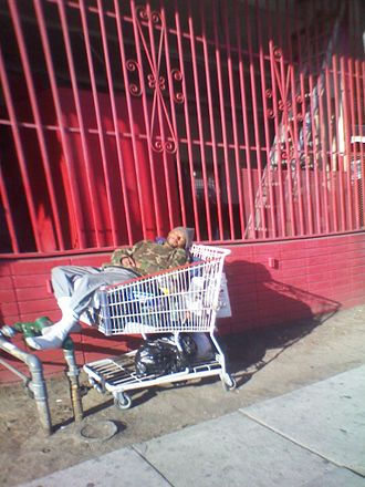 Skid Row, Los Angeles - A man sleeps in a shopping cart on Skid Row, 2012.